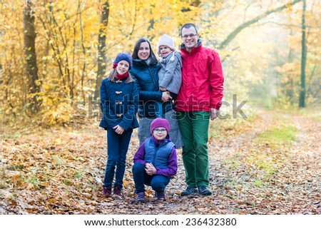 Picture of lovely family in autumn forest, young parents with cute adorable kids, five cheerful persons enjoy autumnal nature