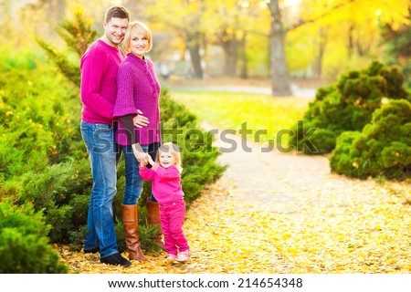 Picture of lovely family in autumn park, young parents with nice adorable kid playing outdoors. Picnic in the autumn park. - stock photo