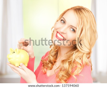 picture of lovely woman with piggy bank and cash money - stock photo