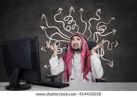 Picture of male Arabian entrepreneur wearing headscarf and looks confused to find solution - stock photo