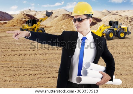 Picture of male engineer wearing helmet and holding blueprints with wheel loader on the construction site