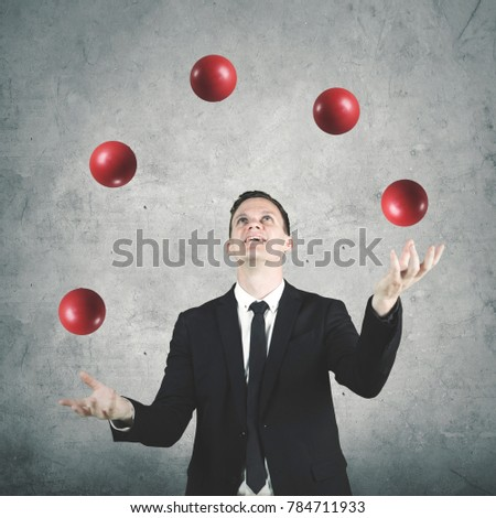 Picture of male entrepreneur wearing formal suit while juggling many red balls
