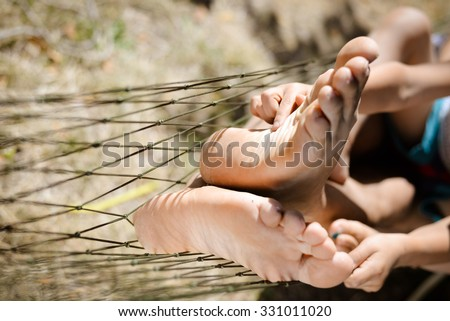 Picture of man and little child's feet resting in hammock. Closeup of happy family tickling and having fun on sunny summer day background. - stock photo