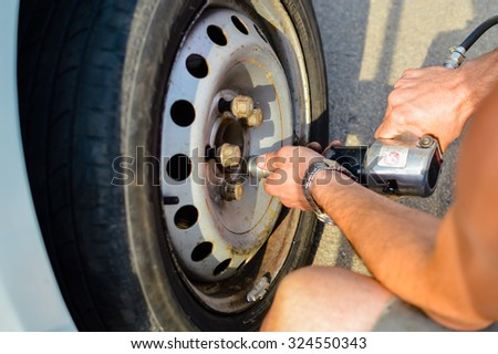 Picture of man beside car changing old wheel. Closeup of hands working with professional screwdriver on blurred sunny outdoor background.