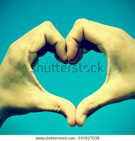 picture of man hands forming a heart over the blue sky, with a retro effect - stock photo