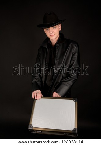 Picture of man in black leather coat with suitcase