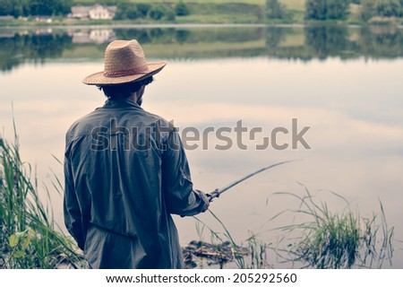 picture of man in straw hat having good time & fun fishing on river bank on peaceful summer day & water outdoors copy space background portrait  - stock photo