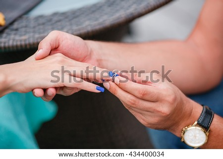 Picture of man putting engagement silver ring on woman hand, outdoor.