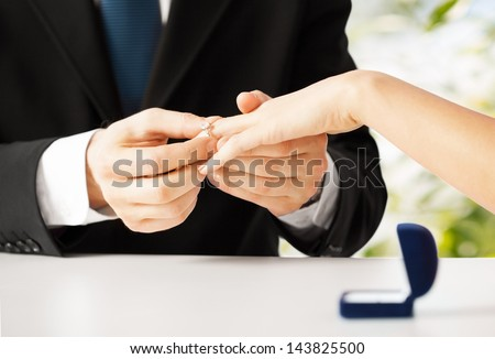 picture of man putting  wedding ring on woman hand - stock photo