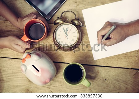 Picture of man's hand writing and woman's hands holding cup of coffee beside piggy-bank and alarm-clock. Top view of  family planning some purchasing on wooden plank table background. - stock photo