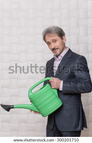 Picture of mature businessman with watering pot. Man in grey business suit knows how to raise his enterprise's profit. - stock photo