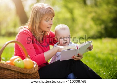 Picture of mature woman with son sitting down on green grass field and read fairytale in park - stock photo