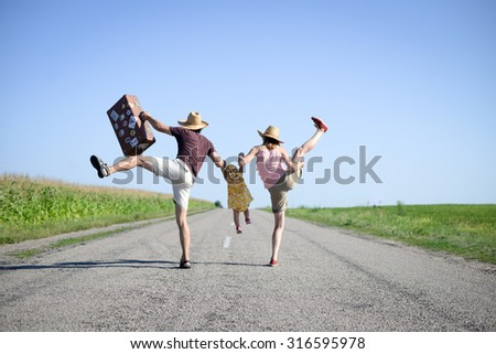 Picture of merry family jumping and dancing on road in summertime. Backview of parents and baby girl with retro suitcase on sunny sky countryside background. - stock photo