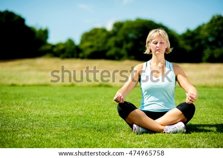 Picture of middle aged Woman meditating on lawn.