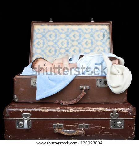 Picture of newborn baby lying in a old suitcase on black background - stock photo