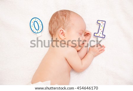 Picture of newborn baby lying in bed on white towel with candle - stock photo