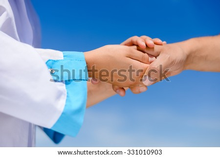 Picture of nurse's hands holding someone's hand with care. Closeup of medicine support on blue sky background.