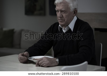Picture of old, sad man without appetite - stock photo
