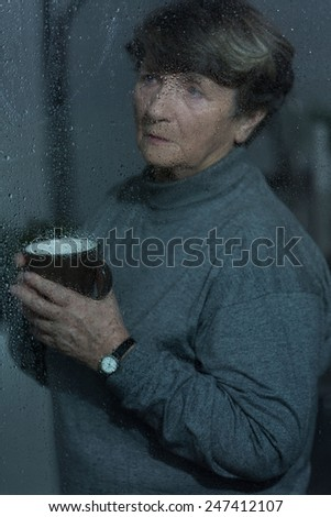 Picture of older grieved woman looking outside