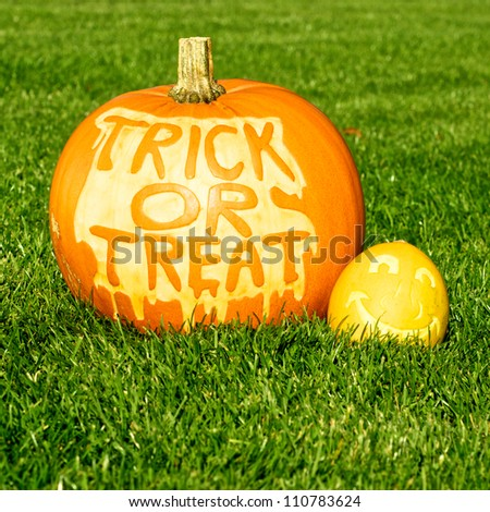 Picture of one big and one small pumpkin, standing on a lawn Small pumpkin has a face cut in the surface, and the big has Trick Or treat cut in the surface - stock photo