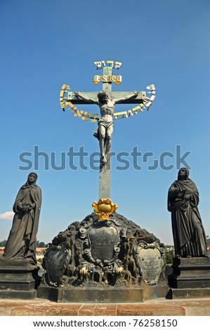 Picture of one stoned cross and two statues on the sides - stock photo