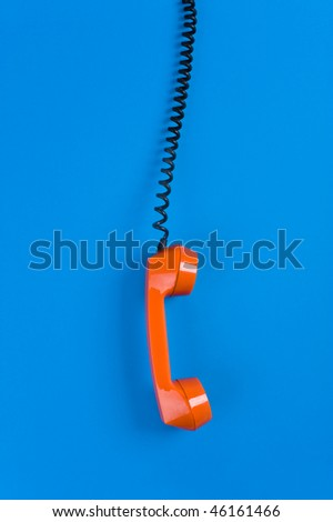 Picture of orange telephone hook over blue background - stock photo