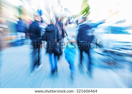 picture of people walking in the city with creative zoom effect made with camera lens