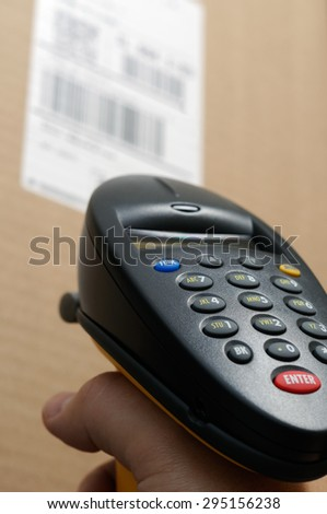 Picture of person's hand holding a barcode scanner reader up to a brown box with a UPC bar code label. - stock photo