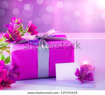 Picture of pink luxury gift box with bouquet of beautiful flowers, romantic candle and postcard with text space on the table, festive still life, blurry background, happy mothers day, spring season - stock photo