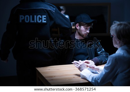 Picture of policeman, young suspect and female police agent - stock photo