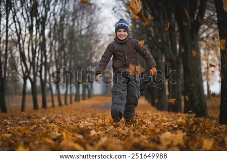 Picture of pretty baby boy running in autumnal park - stock photo