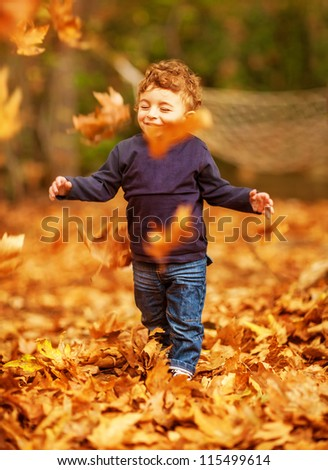 Picture of pretty baby boy running in autumnal park, little child playing with old dry trees foliage, adorable toddler play game on backyard, enjoying walk, beauty autumn season, happy childhood - stock photo