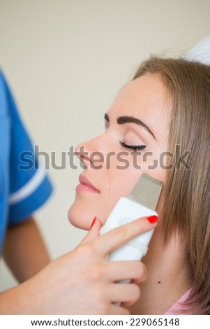 Picture of pretty beautician doing microdermabrasion procedure for young woman laying closed eyes in a beauty salon