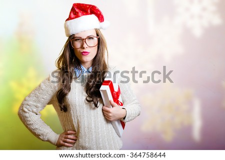 Picture of pretty girl in big glasses and red Santa hat. Young woman stressed and holding gift box on bright festive snowflake background.