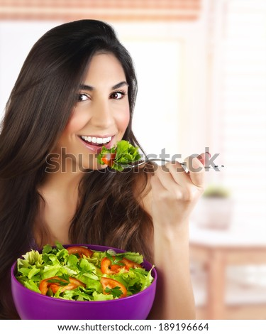 Picture of pretty woman eating green salad, closeup portrait of brunette female holding bowl with fresh vegetables on the kitchen, healthy lifestyle, organic nutrition, dieting concept - stock photo