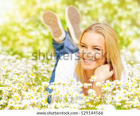 Picture of pretty woman lying down on chamomile field, happy female enjoying spring nature, cheerful girl resting on daisy meadow, beautiful small white flowers, relaxation outdoor in springtime
