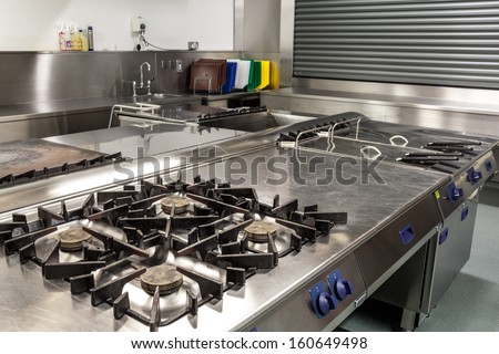 Picture of professional kitchen showing gas stove in foreground