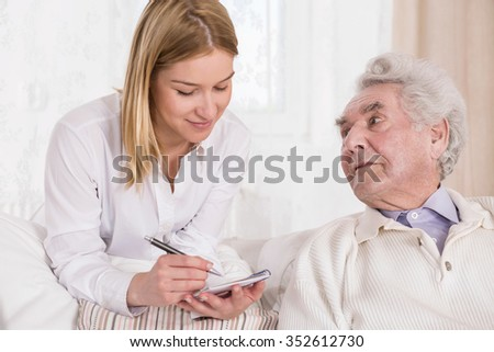 Picture of rich elderly man with private carer - stock photo