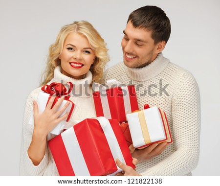 picture of romantic couple in a sweaters with gift boxes