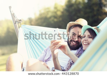 Picture of romantic couple using smartphone in hammock - stock photo