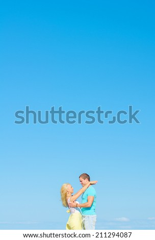 Picture of romantic young couple against blue sky. Space for text.