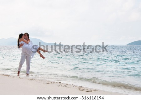 Picture of romantic young couple having a walking on the sea shore - stock photo