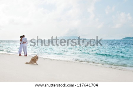 Picture of romantic young couple on the sea shore with dog