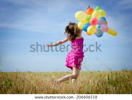 picture of running or walking in the field beautiful blond young woman having fun holding air balloons on summer blue sky outdoors copy space background - stock photo