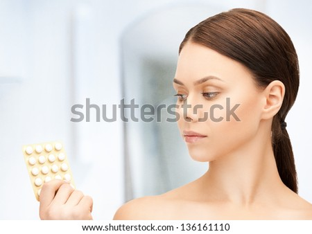 picture of sad young woman with pills - stock photo