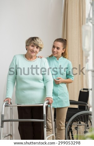 Picture of senior lady with walking problems and helpful carer - stock photo