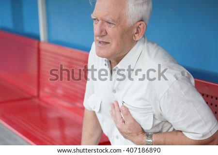 Picture of senior man having heart attack - stock photo