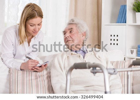 Picture of senior man with walking problem and his carer - stock photo
