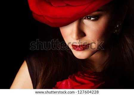 Picture of sexy woman with big red rose hat on the head isolated on black background, closeup portrait of stylish girl with flowers bouquet, Valentine day, beauty and styling salon, elegance concept - stock photo