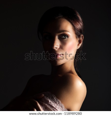 Picture of sexy young lady isolated on black background, stylish woman with dark hair wearing seductive lace dress, pretty female in pink openwork with naked shoulder, sensuality and beauty concept - stock photo